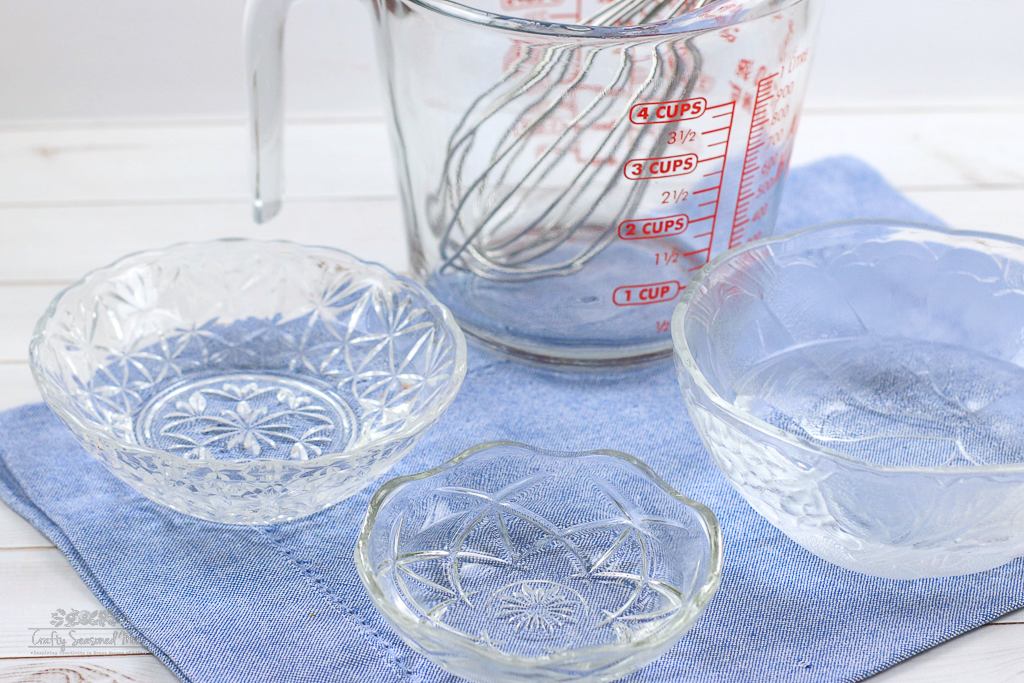 3 glass bowls, and a glass measuring cup with a metal whisk inside for the DIY Natural Disinfectant Spray Recipe