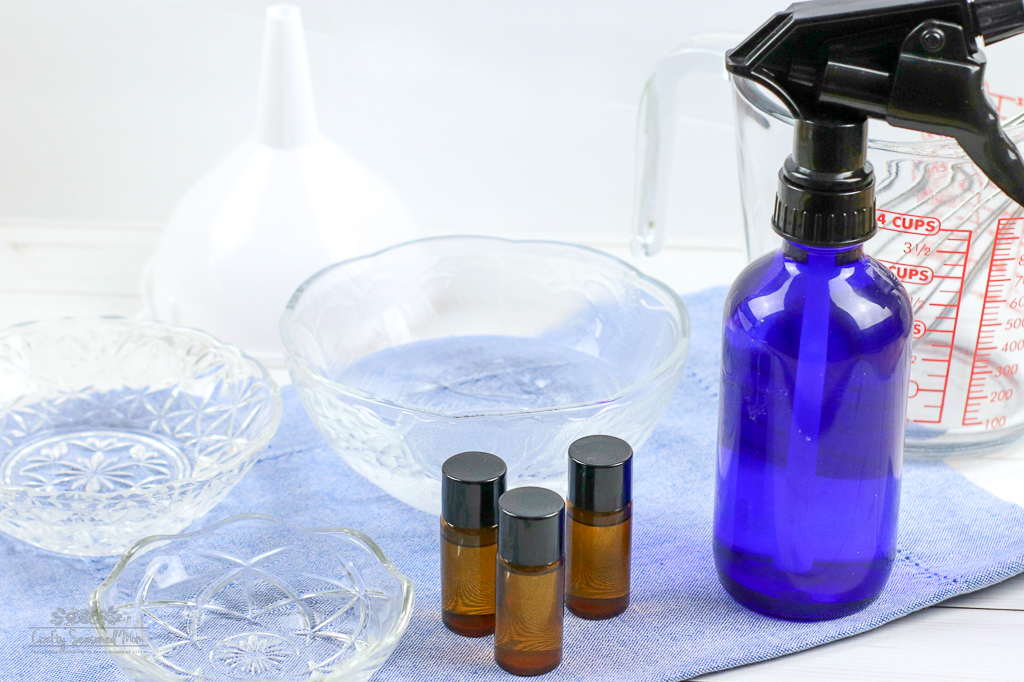 3 glass bowls, 3 small amber bottles and a blue spray bottle for the DIY Natural Disinfectant Spray Recipe