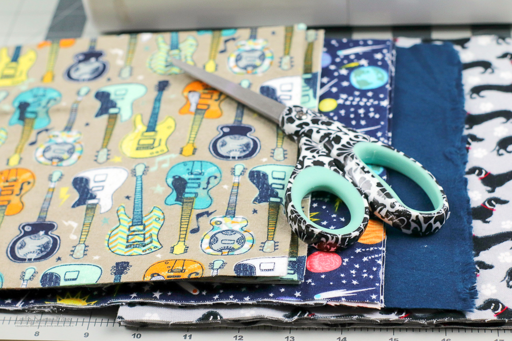 scissors on stacks of fabric for the DIY Reusable Disinfecting Wipes on a grey cutting mat
