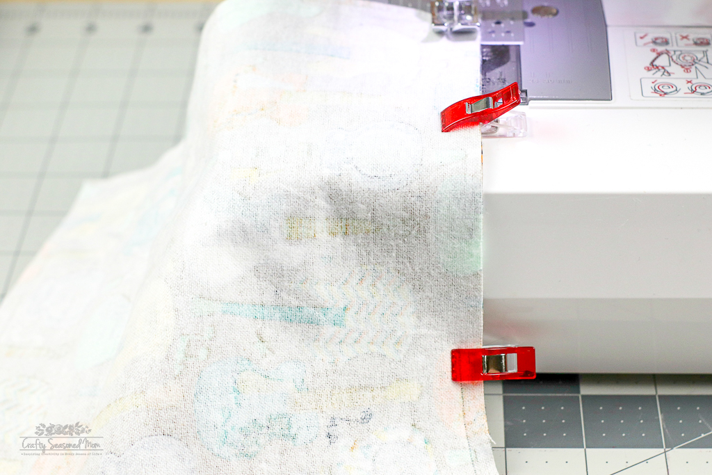 fabric clipped together on a sewing machine for the DIY Reusable Disinfecting Wipes on a grey cutting mat
