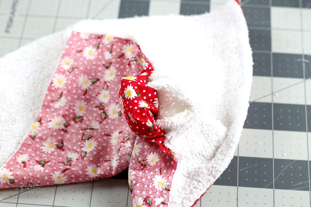 sewn red floral fabric and white terry towel turned inside out on a grey cutting mat for How To Make Reusable Fabric Paper Towels