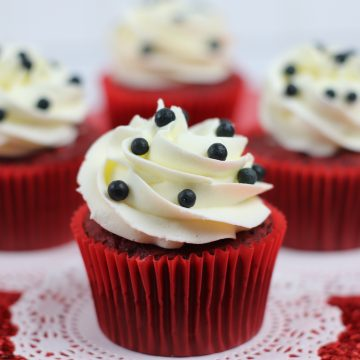 Red Velvet Cupcakes with White Frosting and Black Candies on a doily