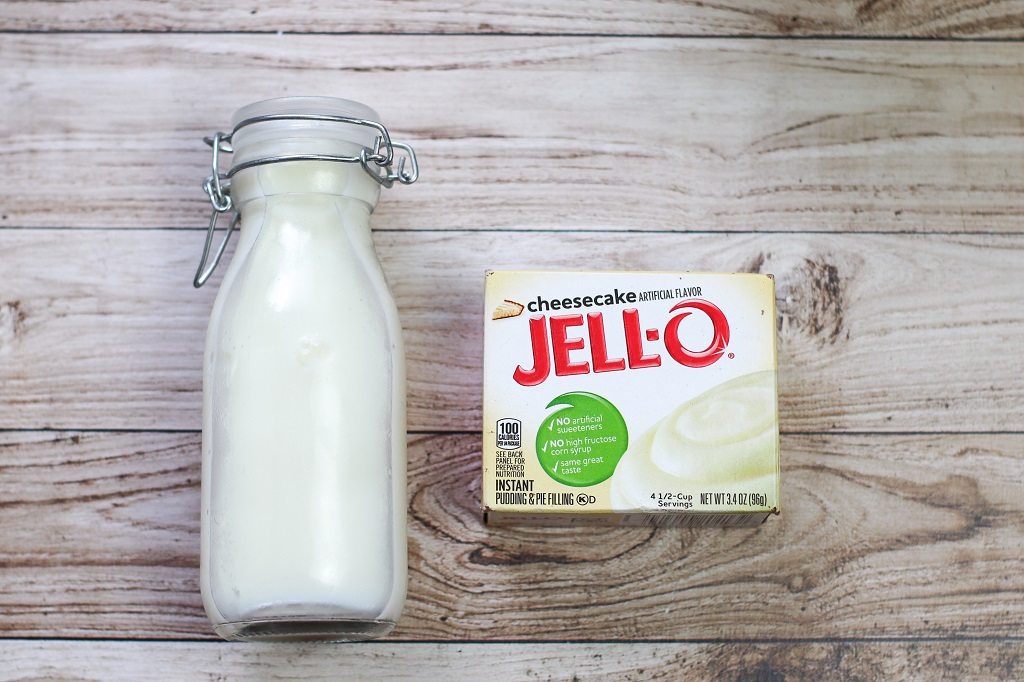 small glass bottle of milk and box of cheesecake jello pudding mix on light wood texture table for swirled mint cheesecake fudge recipe