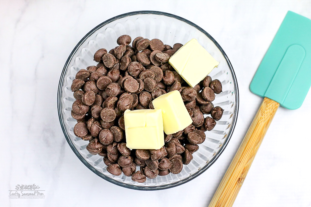 chocolate baking chips and 3 pats of butter in a glass mixing bowl Easy Heath Bar Fudge Recipe